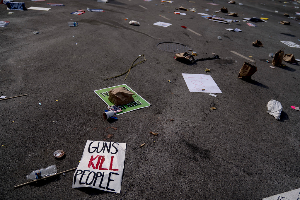 """. Posters and garbage are left strewn along Pennsylvania Avenue following the \""""March for Our Lives\"""" rally in support of gun control in Washington, Saturday, March 24, 2018. (AP Photo/Andrew Harnik)"""