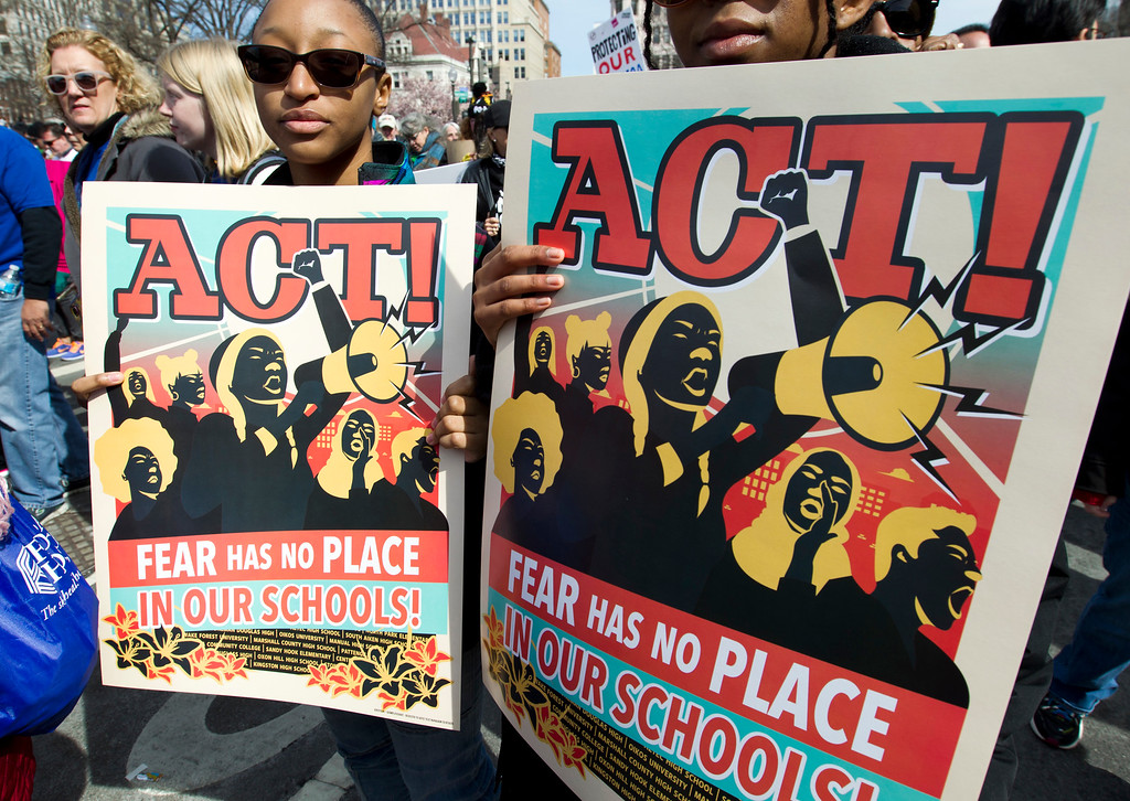 """. Protesters hold signs during the \""""March for Our Lives\"""" rally in support of gun control in Washington, Saturday, March 24, 2018, on Pennsylvania Avenue near the U.S. Capitol. (AP Photo/Jose Luis Magana)"""