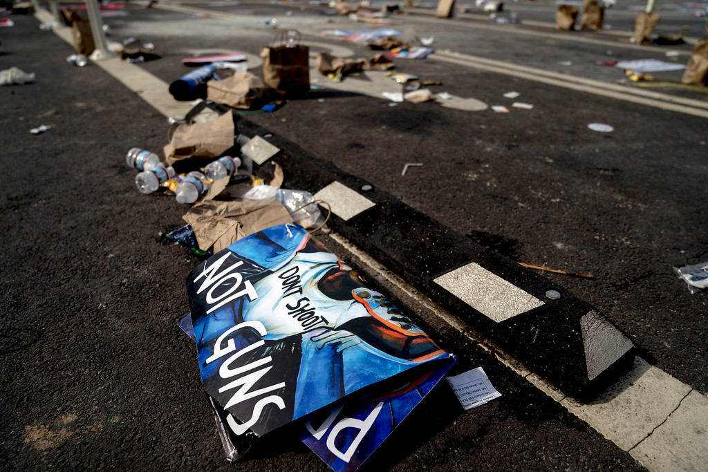 ". Posters and garbage are left strewn along Pennsylvania Avenue following the ""March for Our Lives\"" rally in support of gun control in Washington, Saturday, March 24, 2018. (AP Photo/Andrew Harnik)"