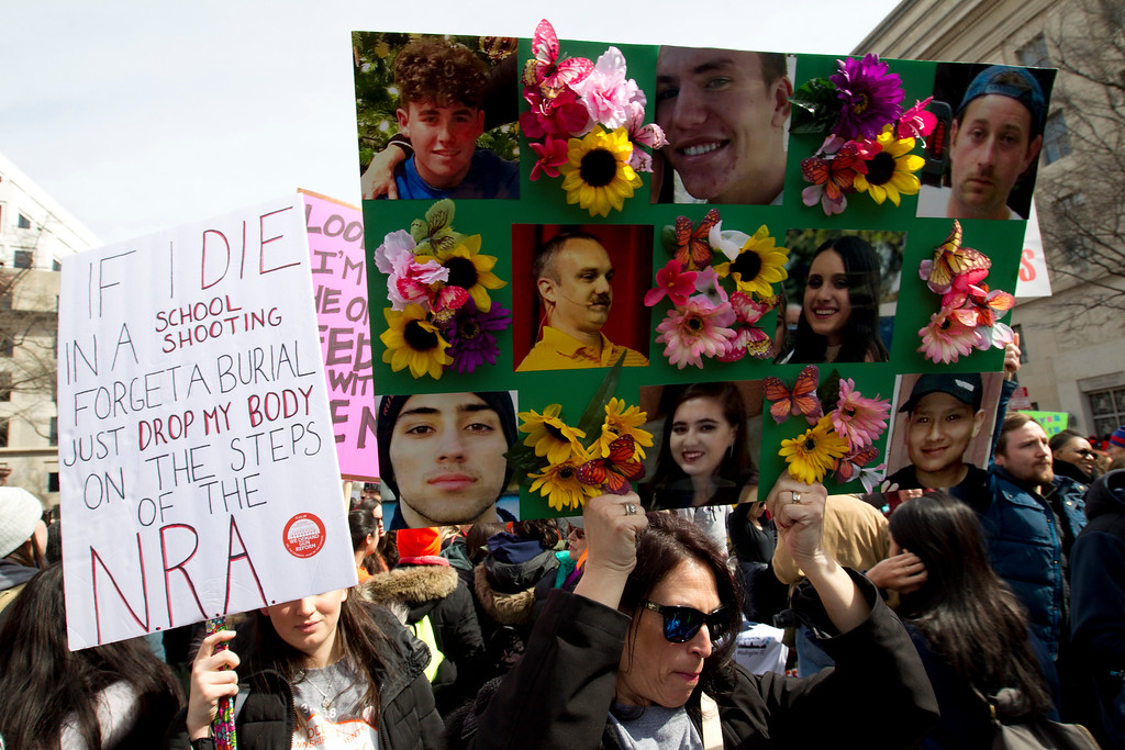 """. A protester holds a sign with pictures of students killed at Marjory Stoneman Douglas High School in Parkland, Fla., during a moment of silence, during the \""""March for Our Lives\"""" rally in support of gun control in Washington, Saturday, March 24, 2018, on Pennsylvania Avenue near the U.S. Capitol. (AP Photo/Jose Luis Magana)"""