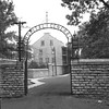 Historic view of the hospital. Note the similarity of the arched sign in this photo with the present-day gate.