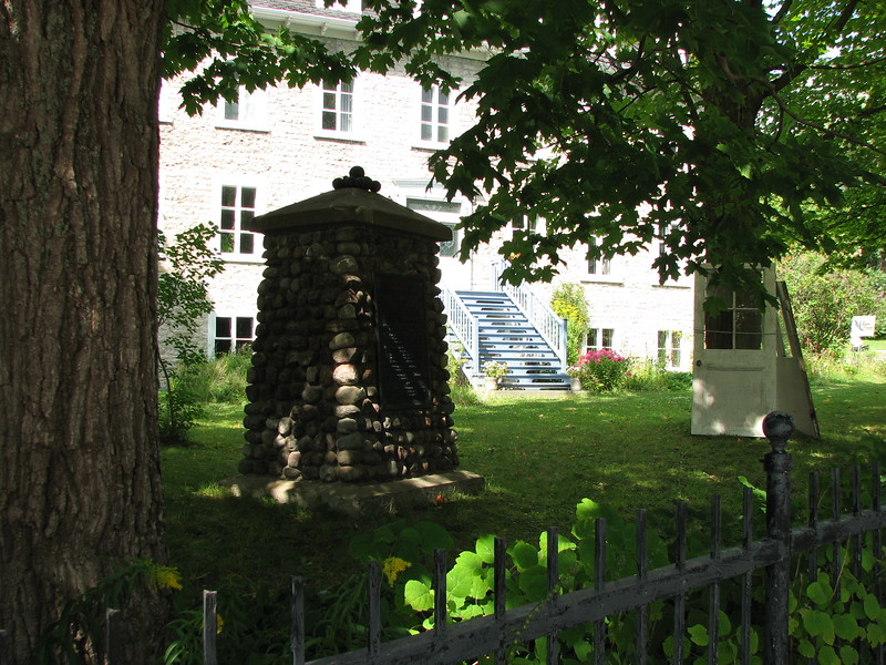 The monument in its setting, on the front lawn of the old convent