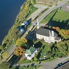 "Aerial view showing the relation of the current manor house (the white building with green roof) to the river and chapel. I believe, based on a drawing of the ruins of the previous manor house seen in this article:  <a href=""http://genealogiestemarie.ca/data/documents/29_Manoirs-Taschereau_002.pdf"">http://genealogiestemarie.ca/data/documents/29_Manoirs-Taschereau_002.pdf</a>  that the manor house Arnold used was probably on the opposite side of the chapel."