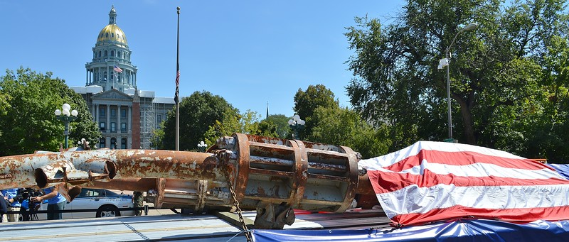 American flag draped over World Trade Center wreckage from 9/11 attack, Colorado capitol building in the background.