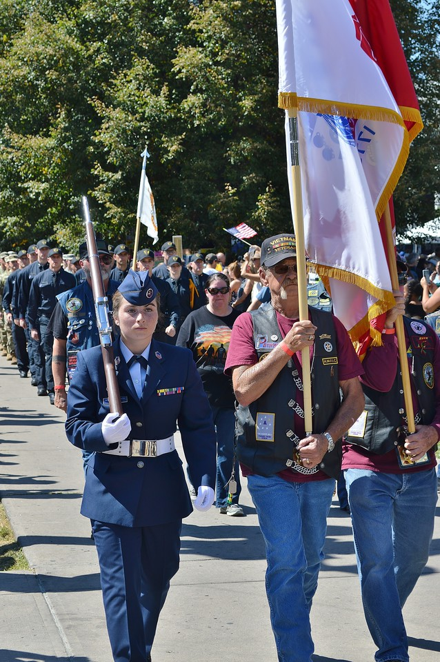 Young woman, member of Civil Air Patrol, marches in 9/11 anniversary commemoration. carrying a rifle, men carrying flags march beside her.