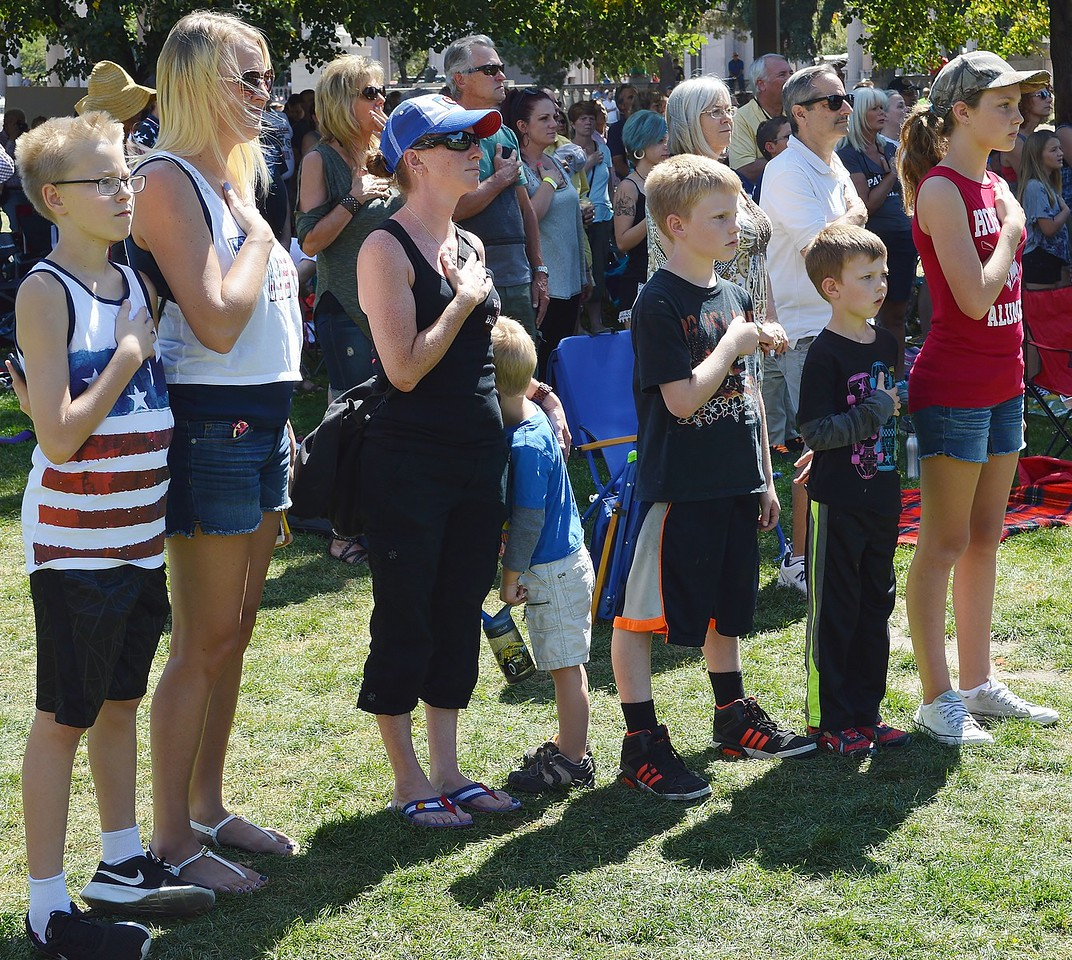 Group of children and mother holding hands over their hearts while national anthem is playing.
