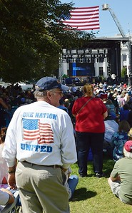 "Man wearing shirt with American flag and slogan ""One Nation United"" at 9/11 anniversary commemoration, large crowd and stage with giant American flag hanging over it in the background."