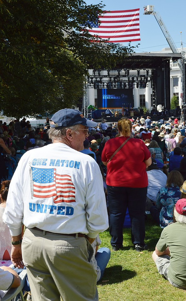 """Man wearing shirt with American flag and slogan """"One Nation United"""" at 9/11 anniversary commemoration, large crowd and stage with giant American flag hanging over it in the background."""