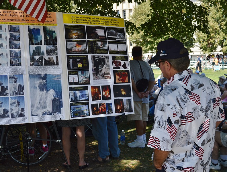 """Man wearing shirt with American flags and slogan """"We The People"""" on it and 9/11 Memorial hat, stands and looks at a display  about 9/11 attack evidence."""