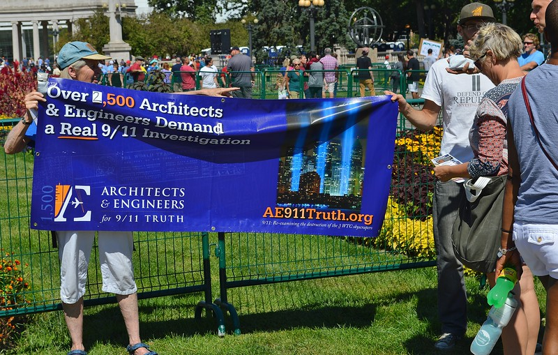 Two people hold up banner about architects & engineers calling for new 9/11 investigation at 9/11 anniversary commemoration in Denver.