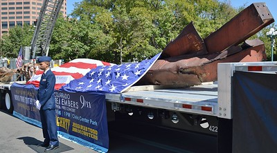 Member of US Air Force  standing in front of 9/11 wreckage displayed on flatbed truck, American flag draped over wreckage.