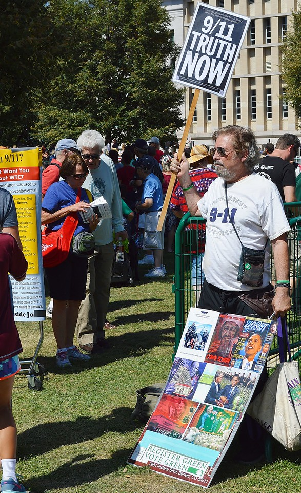 """Man standing behind display about 9/11 attacks, holds up sign  that says """"9/11 Truth Now""""."""