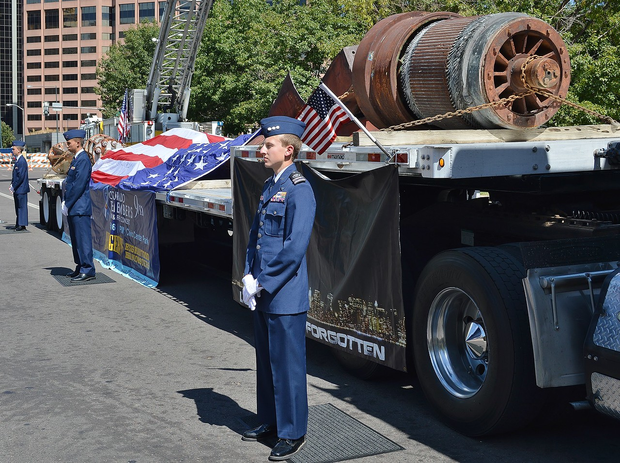 Members of US Air Force standing in front of 9/11 wreckage displayed on flatbed truck.