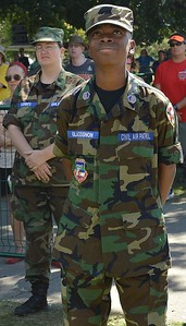 Young African-American man wearing Civil Air Patrol uniform looking up towards the sky, other CAP member behind him.