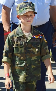 Close-up of young boy in Marine uniform marching in 9/11 anniversary commemoration, members of military marching behind him.