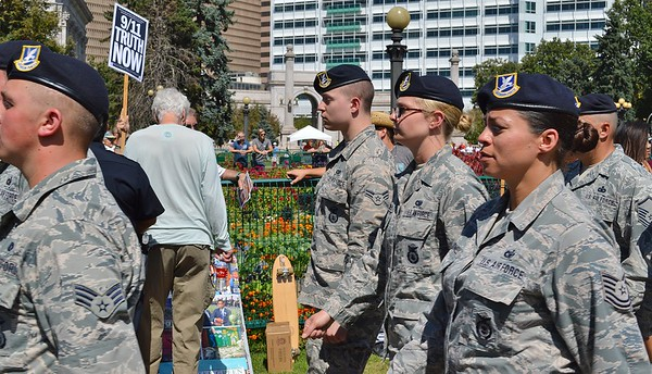 """Members of US Air Force marching in 9/11 anniversary commemoration, man holding """"9/11 Truth Now"""" sign in the background."""