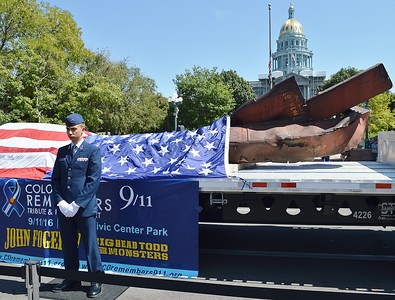 Member of US Air Force  standing in front of 9/11 wreckage displayed on flatbed truck, American flag draped over wreckage, Colorado capitol building in the background.
