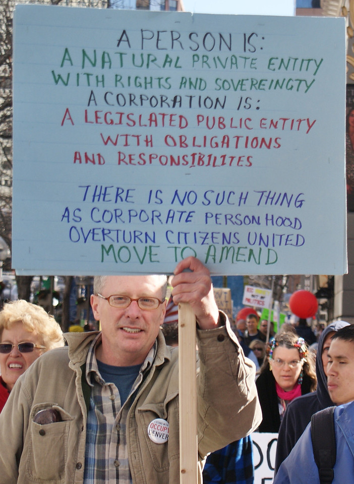 """Denver area residents demonstrate against """"corporate personhood"""" and the """"Citizens United"""" decision by the U.S. Supreme Court, that allowed unlimited corporate spending on elections."""