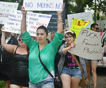 "Young woman holds up ""No Means No"" sign, other anti-rape protesters march behind her."