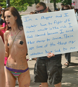 Woman with breasts coverd by tape, carrying a sign about being a stripper and being sexually assualted.