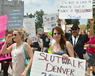 "Young woman holds ""Slutwalk Denver"" sign, others marching behind her with anti-rape signs."