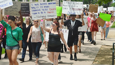 Group of marchers demonstrating against rape, many with signs.