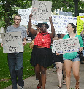 Protesters with anti-rape signs marching down sidewalk.