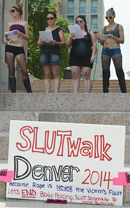 "Four young women reading from sheets of paper at rally, one holding microphone, all wearing ""slut"" costumes, sign below them about ""Denver Slut Walk""."