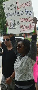 African-American woman holds up sign about sexual assualt in the USA.