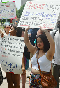 "Young woman holds up sign ""Consent Is Sexy"", woman beside her with ""Slutwalk"" sign."