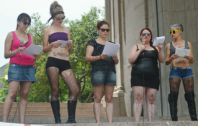 "Four young women reading from sheets of paper at rally, two holding microphones, all wearing ""slut"" costumes, some with writing on their bodies."