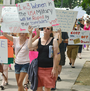 Woman marching with sign about rape in the military, other demonstrators marching behind her.