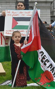 Young girl standing next to Palestine banner, holding Palestinian flag.