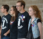 Four high school students standing on stage together at school protest, all wearing buttons or t-shirts.