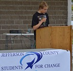 Young man, a high school student, speaking from a podium, sign in foreground says