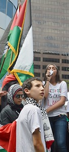 Young woman speaks using bullhorn, Palestinian flags next to her, young boy and woman wearing headscarf in foreground.