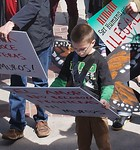 Young boy looks down at sign he is holding at immigration reform protest.