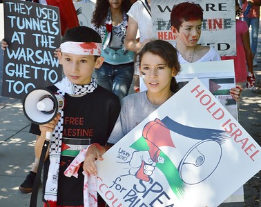 Young boy and girl march in protest over Israeli attacks on Gaza, boy holding small bullhorn, other demonstrators in background.
