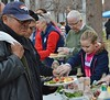 Man wearing Denver Broncos hat holding plate of food at free meal event. On other side of table, young girl and senior woman serving food to others in line.
