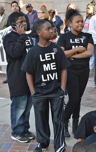 "Three young children wearing t-shirts that read ""Let Me Live"", one speaking on a cellphone."