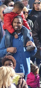 African-American father carrying son on shoulders during MLK Day parade in Denver.