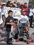 Hispanic mother and three children, one in stroller, one holding sign at immigration reform rally.