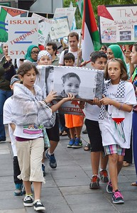 Young girls and boys carrying a mock coffin with photographs on side, some wearing keffiyehs, protest marchers with signs and Palestinian flags in background.