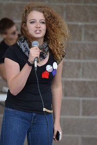 Young girl, a high school student, standing on stage speaking into microphone, holding a cellphone, wearing protest buttons.
