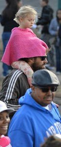 Young girl wearing pink sweater riding on top of her father shoulders at MLK Day parade.