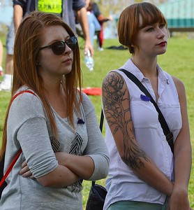 Two young girls, high school students, standing together listening, one with large tatoo of tree on her arm.
