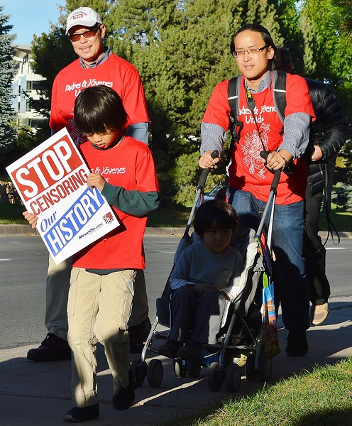 Young Asian-American boy carries sign about censoring history, behind  man pushing child in stroller.