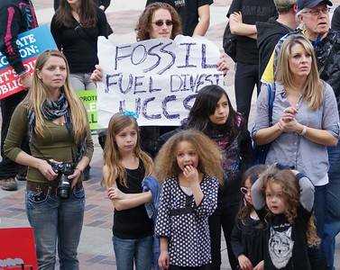 "Two women and 4 young children listen at climate change rally, man behind them with ""fossil fuel divest' sign."