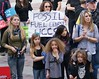 """Two women and 4 young children listen at climate change rally, man behind them with """"fossil fuel divest' sign."""