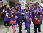 Two women and three young girls, all wearing Justice for Janitors t-shirts marching together, one girl has hat on sideways, other protesters behind them.